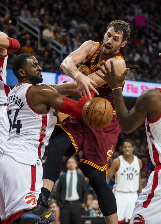 . Cleveland Cavaliers\' Kevin Love, center, bottles Toronto Raptors\' Patrick Patterson (54) for a rebound during the first half of an NBA basketball game in Cleveland, Tuesday, Nov. 15, 2016. (AP Photo/Phil Long)