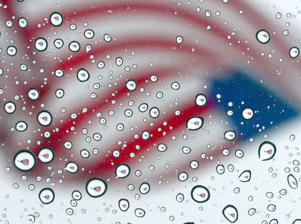 . An American flag flying at Uptown Station shopping center is reflected in rain drops on Thursday, July 4, 2013 in Fort Walton Beach, Fla. (AP Photo/Northwest Florida Daily News, Nick Tomecek)