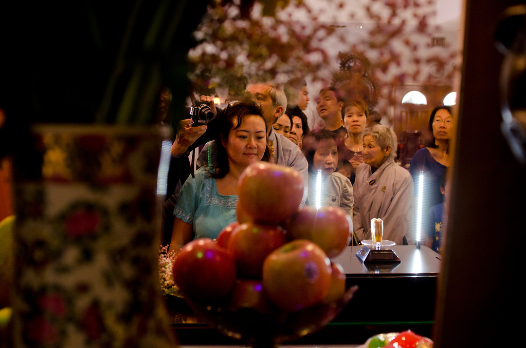 . A crowd gets an up-close look at a rare tooth relic of Shakyamuni Buddha on the table at Lu Mountain Temple in Rosemead, Calif., Sunday, March 31, 2013. Several shariras were made available for viewing to the public including the rare tooth relic measuring about two inches in height. (SGVN/Correspondent photo by Anibal Ortiz)