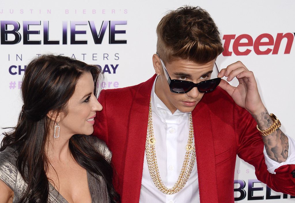""". Singer Justin Bieber (R) and mother Pattie Mallette attend the world premiere of \""""Justin Bieber\'s BELIEVE,\"""" December 18, 2013 at the Regal Cinemas at LA Live in Los Angeles, California.  The film opens nationwide on Christmas Day.         (ROBYN BECK/AFP/Getty Images)"""