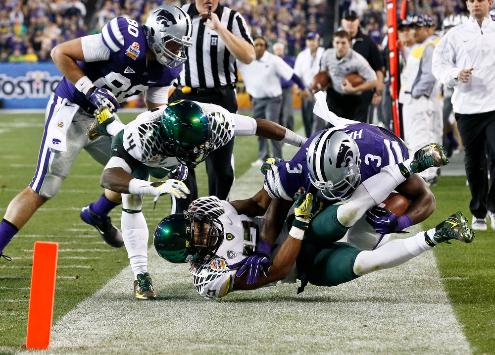 . Kansas State\'s Chris Harper (3) gets tackled out of bounds by Oregon\'s Brian Jackson (12) and Ifo Ekpre-Olomu (14) as Kansas State\'s Travis Tannahill (80) watches during the first half in the Fiesta Bowl NCAA college football game, Thursday, Jan. 3, 2013, in Glendale, Ariz. (AP Photo/Ross D. Franklin)