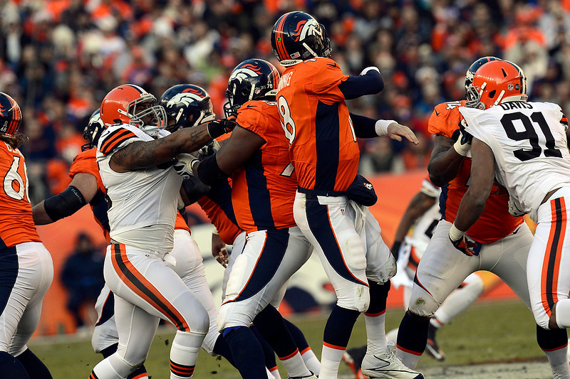 . Denver Broncos quarterback Peyton Manning (18) gets hit from behind resulting in an incomplete pass during the first half.  The Denver Broncos vs Cleveland Browns at Sports Authority Field Sunday December 23, 2012. Joe Amon, The Denver Post