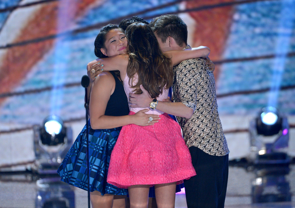 """. The cast of \""""Glee\"""", from left, Jenna Ushkowitz, Lea Michele and Kevin McHale hug on stage at the Teen Choice Awards at the Gibson Amphitheater on Sunday, Aug. 11, 2013, in Los Angeles. (Photo by John Shearer/Invision/AP)"""