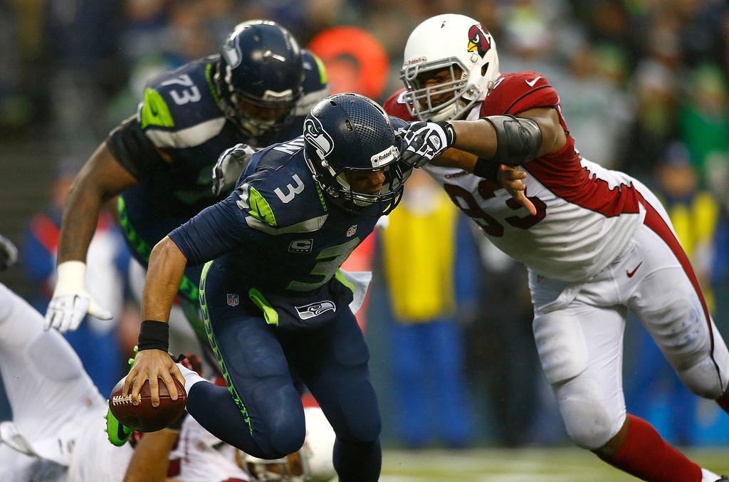 . Russell Wilson #3 of the Seattle Seahawks is pressured by Calais Campbell #93 of the Arizona Cardinals on December 22, 2013 at CenturyLink Field in Seattle, Washington.  (Photo by Jonathan Ferrey/Getty Images)