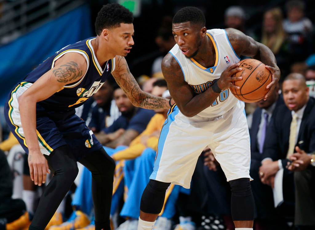 . Denver Nuggets guard Nate Robinson, right, looks to pass the ball as Utah Jazz guard Diante Garrett covers in the third quarter of Utah\'s 103-93 victory in an NBA basketball game in Denver on Friday, Dec. 13, 2013. (AP Photo/David Zalubowski)