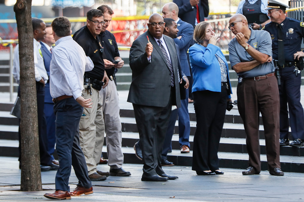. Cincinnati Police Chief Eliot Isaac, center, works the scene as emergency personnel and police respond to reports of a shooting near Fountain Square, Thursday, Sept. 6, 2018, in downtown Cincinnati. (AP Photo/John Minchillo)