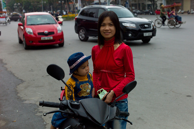 Mom, son and motorbike at the curb, near the Hanoi Opera House.