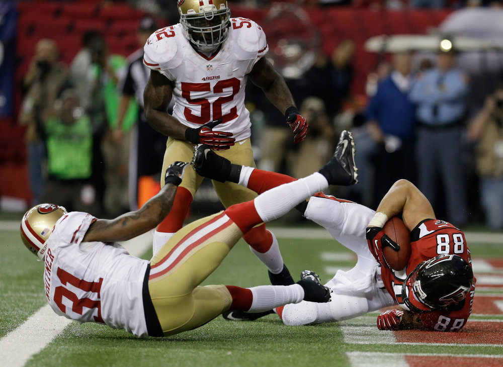 Description of . Atlanta Falcons\' Tony Gonzalez catches a 10-yard touchdown pass in front of San Francisco 49ers\' Donte Whitner (31) during the first half of the NFL football NFC Championship game Sunday, Jan. 20, 2013, in Atlanta. Center is 49ers Patrick Willis. (AP Photo/Mark Humphrey)