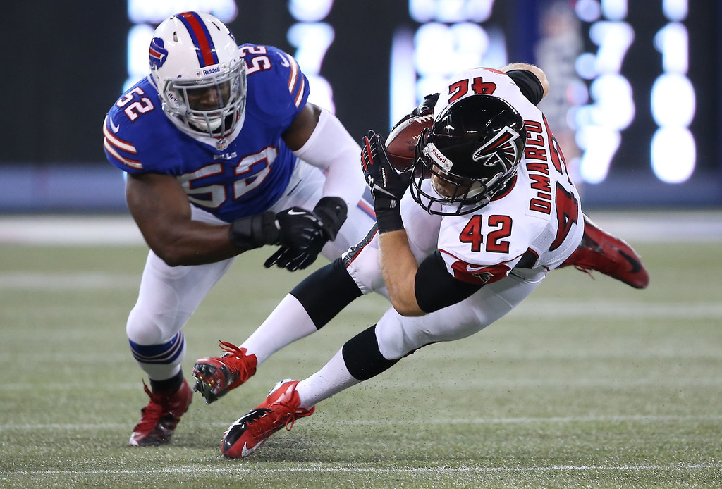 . Patrick DiMarco #42 of the Atlanta Falcons is tackled during an NFL game by Arthur Moats #52 of the Buffalo Bills at Rogers Centre on December 1, 2013 in Toronto, Ontario. (Photo by Tom Szczerbowski/Getty Images)