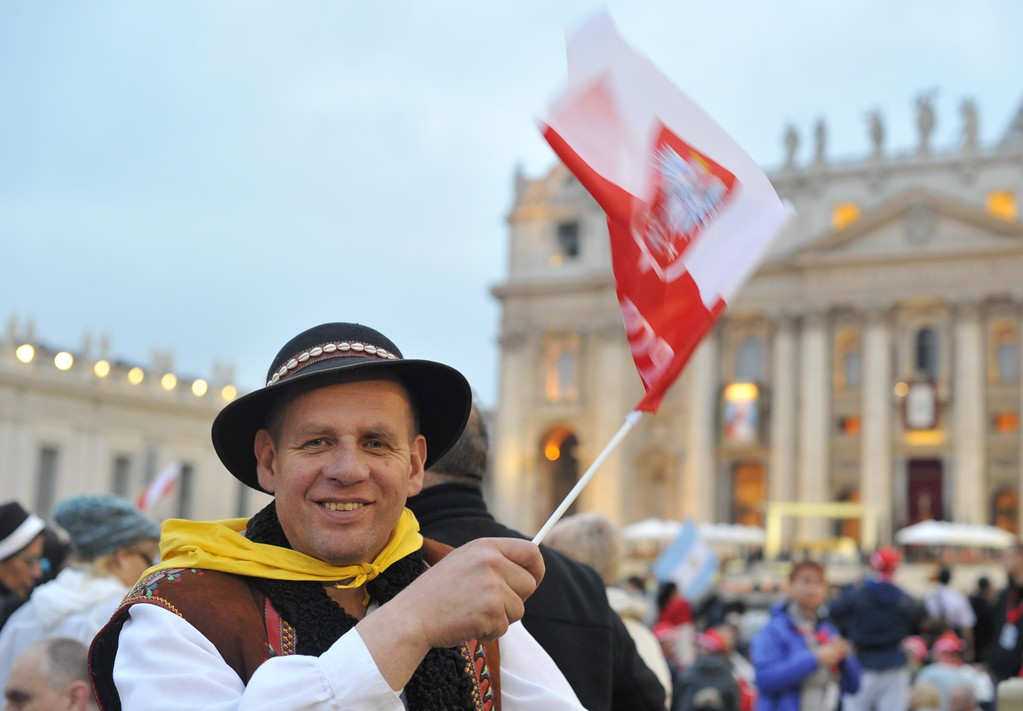 . A man waves a Polish flag as he arrive for the canonisation mass of Popes John XXIII and John Paul II on St Peter\'s at the Vatican on April 27, 2014. Catholics from around the world gathered in Rome on Sunday for a mass presided by Pope Francis to confer sainthood on John Paul II and John XXIII -- two influential popes who helped shape 20th century history.    AFP PHOTO / TIZIANA FABI