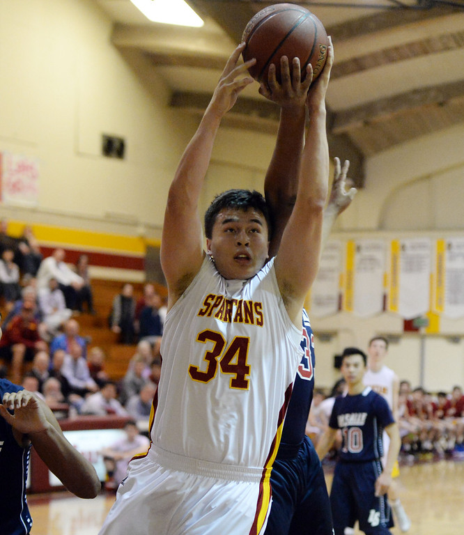 . La Canada\'s Kyle Thomas (34) rebounds in front of La Salle\'s Chris Robinson in the first half of a prep basketball game at La Canada High School in La Canada, Calif., on Friday, Jan. 10, 2014. La Canada won 73-62. (Keith Birmingham Pasadena Star-News)