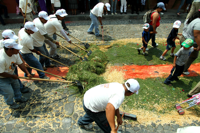 A clean up crew moves quickly to remove carefully crafted alfombras that are laid out for processioners to walk over during Lent in Antigua, Guatemala on March 24, 2013. Photo by Scott Umstattd