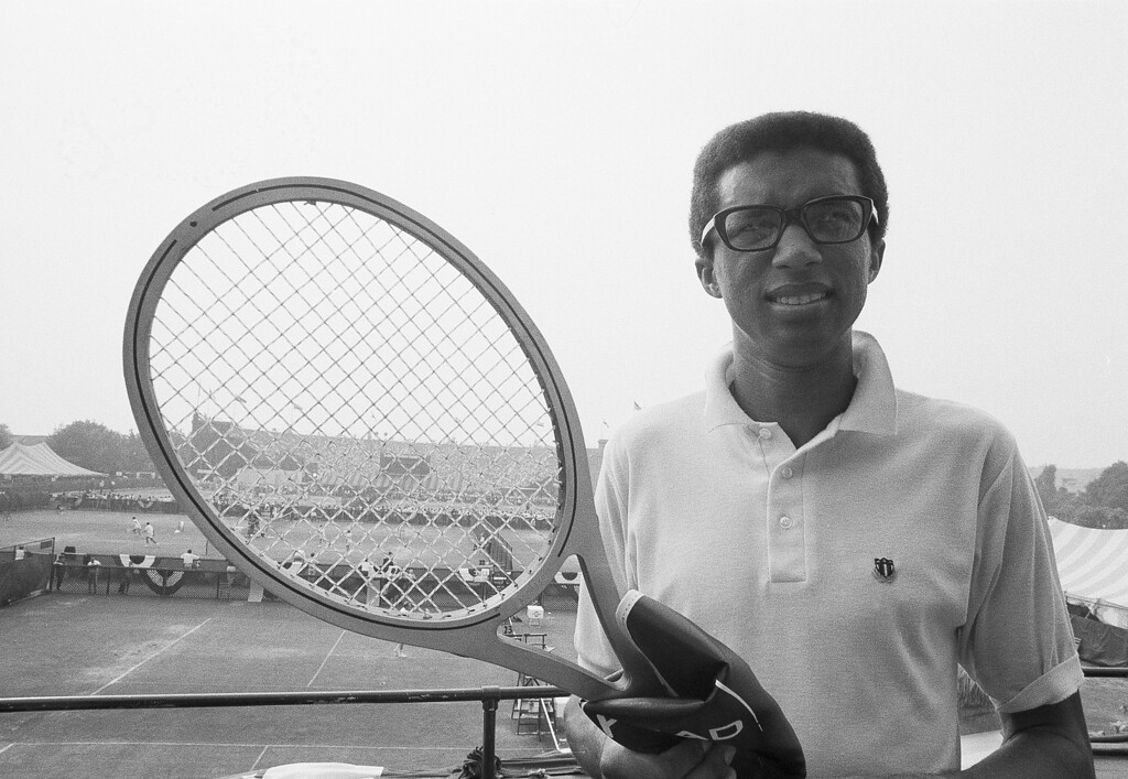 ". Tennis star Arthur Ashe, the number 1 U.S. Davis Cup player from Richmond, Va., poses with his new racket, Aug. 31, 1969, at Forest Hills, N.Y., where he is competing in the $137,000 U.S. Open tennis championship. The racket is gray in color and his made of layers of glass, aluminum and wood. ""It\'s what they call a sandwich,\"" said Ashe.  (AP Photo/Harry Harris)"
