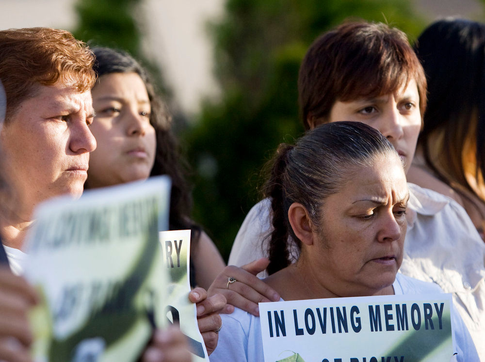 . Friends and family hold signs and candles during a news conference to talk about the death of Ricardo Portillo, who passed away after injuries he sustained after an assault by a soccer player at a soccer game he was refereeing on April 27, in Salt Lake City on Sunday, May 5, 2013. (AP Photo/The Salt Lake Tribune, Kim Raff)