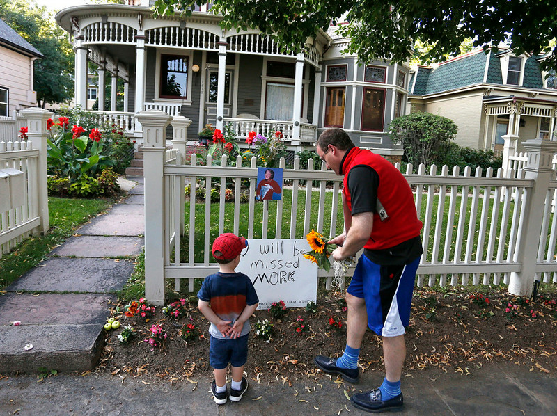 ". U.S. Rep. Jared Polis, D-Colo., and his son AJ leave flowers at the home where the 80\'s TV series ""Mork & Mindy\"", starring the late Robin Williams, was set, in Boulder, Colo., Monday Aug. 11, 2014. Robin Williams, the Academy Award winner and comic supernova whose explosions of pop culture riffs and impressions dazzled audiences for decades and made him a gleamy-eyed laureate for the Information Age, died Monday in an apparent suicide. He was 63. (AP Photo/Brennan Linsley)"