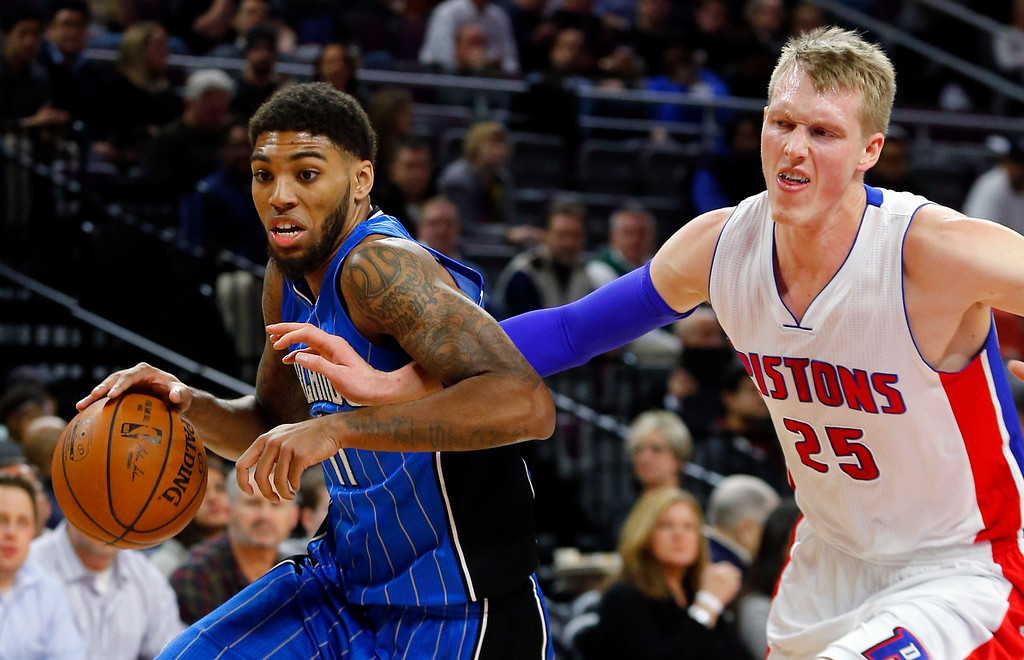 . Orlando Magic guard Devyn Marble (11) drives against Detroit Pistons forward Kyle Singler (25) in the first half of an NBA basketball game in Auburn Hills, Mich., Wednesday, Jan. 21, 2015. (AP Photo/Paul Sancya)