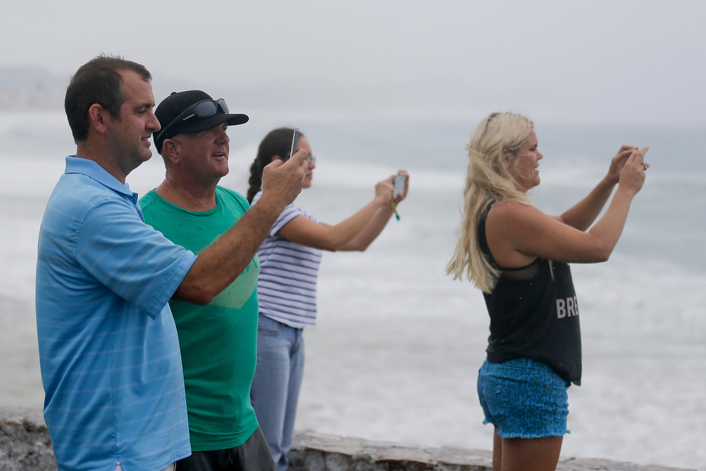 . People take photos of the sea in Los Cabos, Mexico, Sunday, Sept. 14, 2014. Hurricane Odile grew into a major storm Sunday and took aim at the resort area of Los Cabos, prompting Mexican authorities to evacuate vulnerable coastal areas and prepare shelters for up to 30,000 people. (AP Photo/Victor R. Caivano)