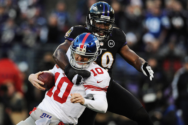 . Quarterback Eli Manning #10 of the New York Giants is pulled down by linebacker Dannell Ellerbe #59 of the Baltimore Ravens in the first quarter at M&T Bank Stadium on December 23, 2012 in Baltimore, Maryland. (Photo by Patrick Smith/Getty Images)