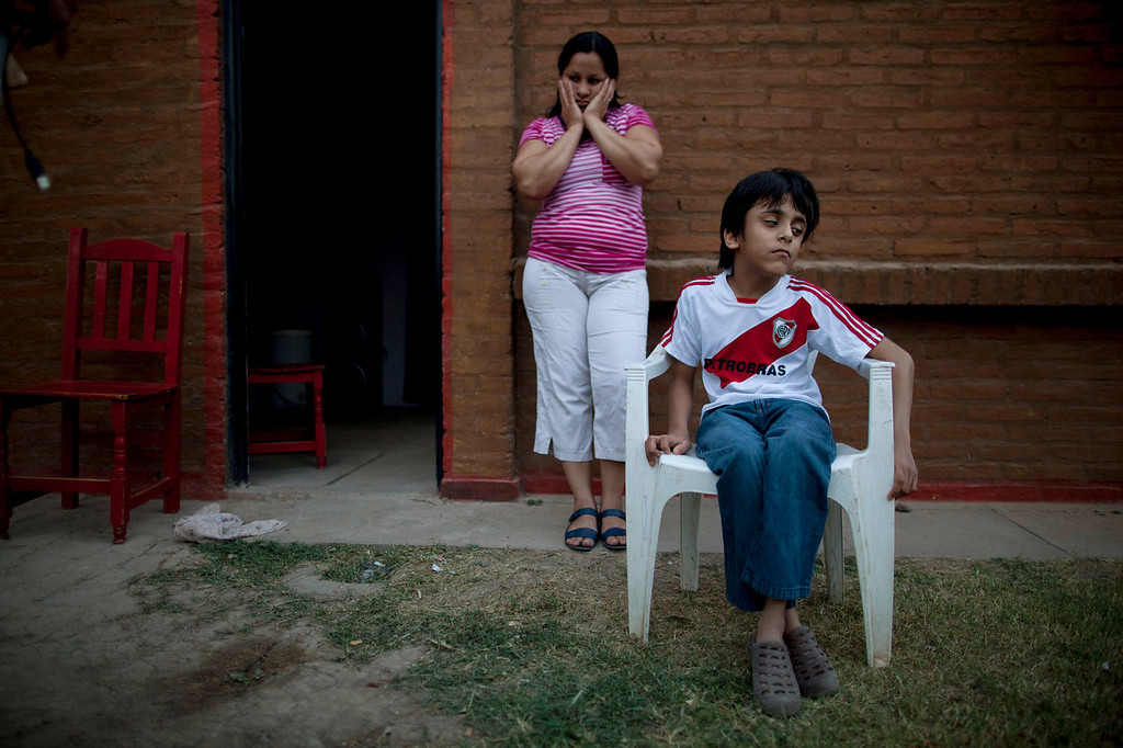 . Silvia Alvarez leans against her red brick home while keeping an eye on her son, Ezequiel Moreno, who was born with hydrocephalus, in Gancedo, in Chaco province, Argentina on April 1, 2013. Alvarez blames continuous exposure to agrochemical spraying for two miscarriages and her son\'s health problems. Chaco provincial birth reports show that congenital defects quadrupled in the decade after genetically modified crops and their related agrochemicals arrived. (AP Photo/Natacha Pisarenko)