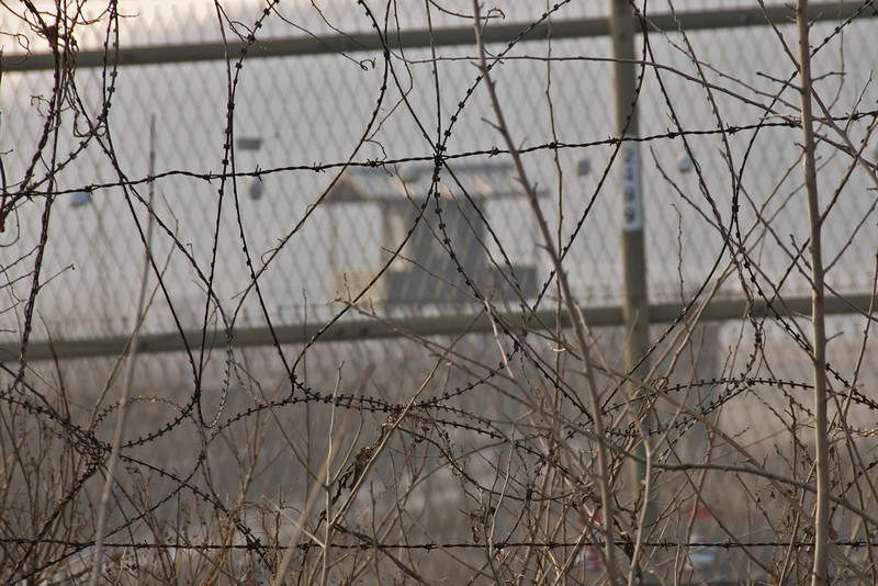 Close-up on barbed wires and guard tower on the background - DMZ, South Korea