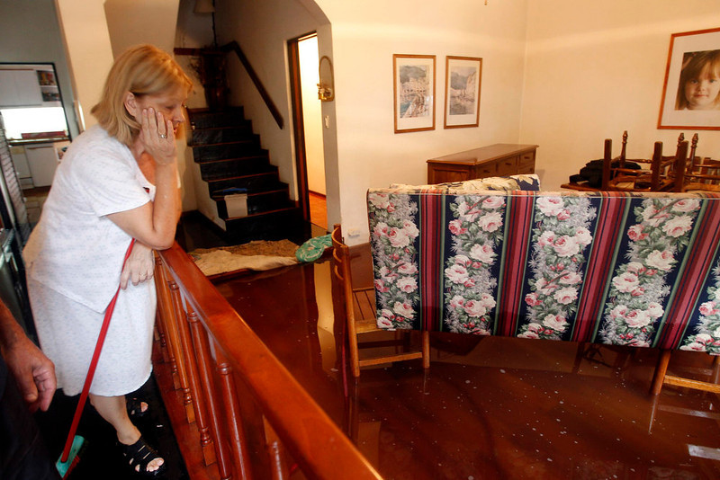 . A woman looks at the flooded living room of her home after a rainstorm in Buenos Aires April 2, 2013. Thunderstorms damaged property and vehicles, cut power and caused delays on flights in Buenos Aires and its suburbs. The City\'s SAME emergency service announced that the death toll has risen to five.     REUTERS/Enrique Marcarian