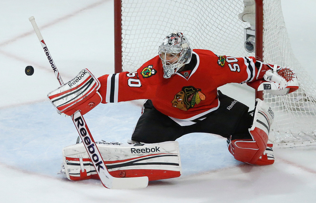 . Chicago Blackhawks goalie Corey Crawford deflects a shot by the Los Angeles Kings during the third period in Game 1 of the NHL hockey Stanley Cup Western Conference finals Saturday, June 1, 2013, in Chicago. Chicago won 2-1. (AP Photo/Charles Rex Arbogast)