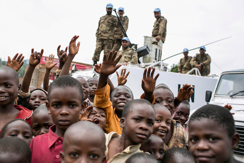 ". Congolese children gather in front of a United Nations peacekeeping tank during the global rally ""One Billion Rising\"" which is part of a V-Day event calling for an end to gender-based violence, in Bukavu February 14, 2013. V-Day is a global activist movement to end violence against women and girls. REUTERS/Jana Asenbrennerova"
