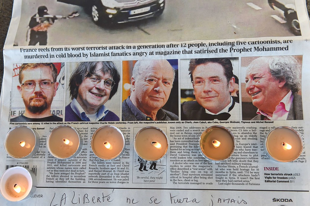 . Candles are placed on a newspaper bearing pictures from (L) of French satirical weekly Charlie Hebdo\'s editor and cartoonists Charb, Jean Cabut, aka Cabu, Georges Wolinski and Michel Renaud who were killed the day before in an attack by two armed gunmen on the offices of French satirical newspaper Charlie Hebdo, during a gathering in Marseille, on January 8, 2015. A stunned and outraged France was in mourning yesterday, as security forces desperately hunted two brothers suspected of gunning down 12 people in an Islamist attack on a satirical weekly. AFP PHOTO / ANNE-CHRISTINE POUJOULAT/AFP/Getty Images