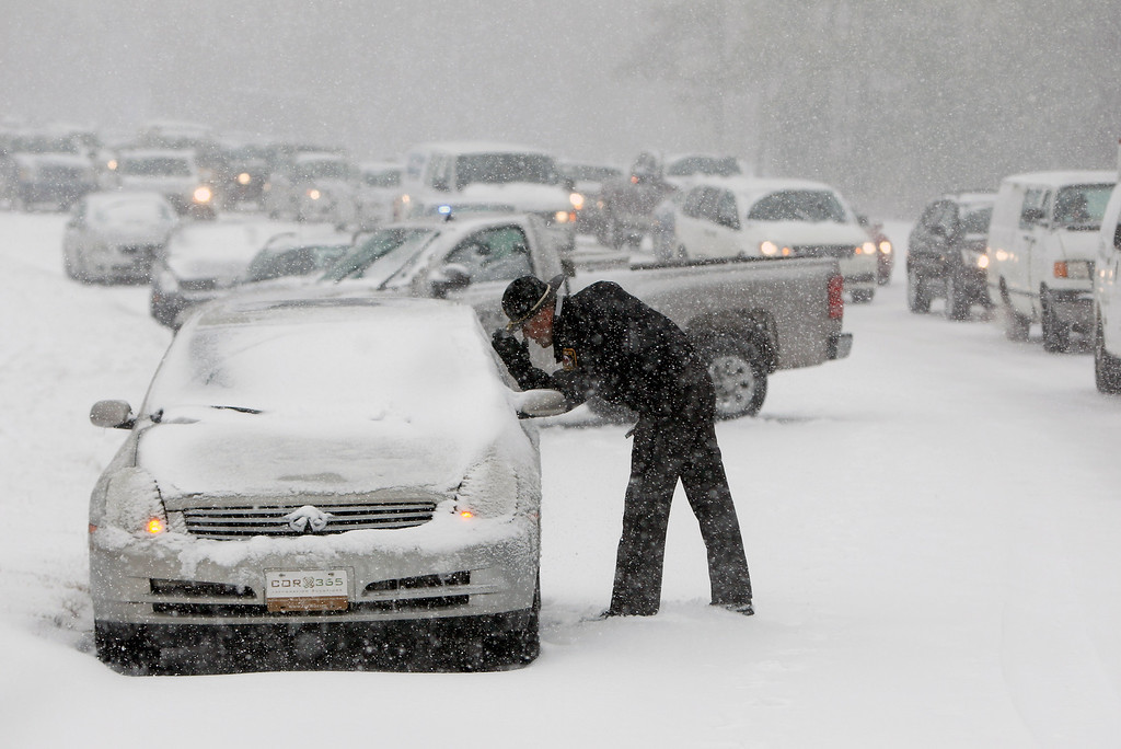 . A Highway Patrol officer checks on the safety of a stranded motorist on Hammond Road during a winter storm Wednesday Feb. 12, 2014, in Raleigh, N.C. (AP Photo/The News & Observer, Travis Long)