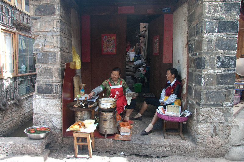One of many small businesses selling food in front of their house.This lady was frying small fish that she sells in skewers.