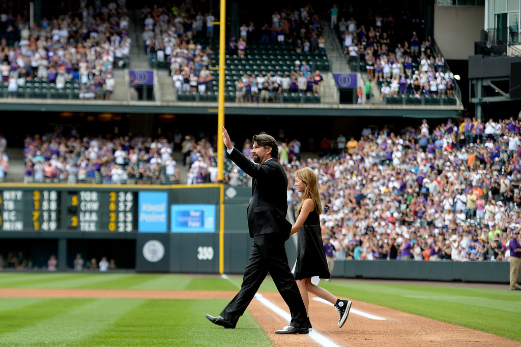 . Colorado Rockies great Todd Helton walks onto the field with his daughter, Tierney Faith, during a retirement ceremony for his number 17. Helton, who played 17 season with the Rockies and holds records for many of the organizations career statistics, was honored on Sunday, August 17, 2014. (Photo by AAron Ontiveroz/The Denver Post)