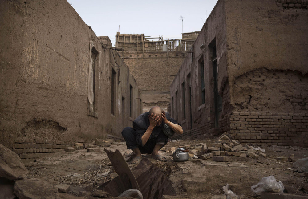 . KASHGAR, CHINA - JULY 27:  A Uyghur man washes himself before prayers next to abandoned traditional houses set to be demolished by authorities to make way for new homes on July 27, 2014 in old Kashgar, Xinjiang Province, China. Nearly 100 people have been killed in unrest in the restive Xinjiang Province in the last week in what authorities say is terrorism but advocacy groups claim is a result of a government crackdown to silence opposition to its policies. China\'s Muslim Uyghur ethnic group faces cultural and religious restrictions by the Chinese government. Beijing says it is investing heavily in the Xinjiang region but Uyghurs are increasingly dissatisfied with the influx of Han Chinese and uneven economic development.  (Photo by Kevin Frayer/Getty Images)