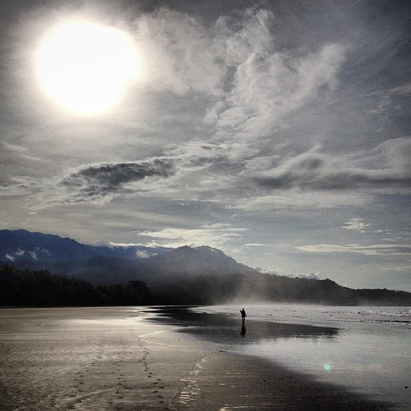 A long, low-tide sunrise walk along Bahia Ballena, Costa Rica with all the trimmings: steam and mist off the sand, clouds rising from the jungle behind and a lone beachcomber at the water's edge.