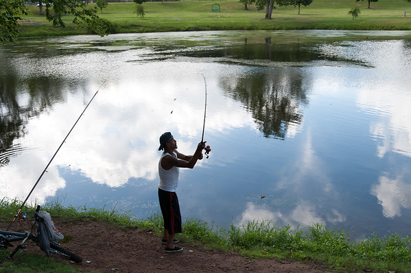 07/24/18 Wesley Bunnell | Staff Blue sky and clouds are reflected at Stanley Quarter Park on Tuesday afternoon as Ramon Rodriguez casts the second line from his two fishing poles.