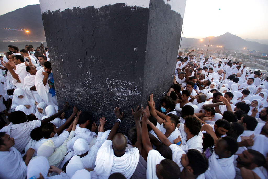 . Muslim pilgrims touch a marker at the top of a rocky hill called the Mountain of Mercy, near the holy city of Mecca, Saudi Arabia, Monday, Oct. 14, 2014. The trek to the site is itself the answer to a lifetime of prayers for many Muslims. Hajj is a central pillar of Islam and the pilgrimage is one that all able-bodied Muslims are required to perform once in their lives.(AP Photo/Amr Nabil)