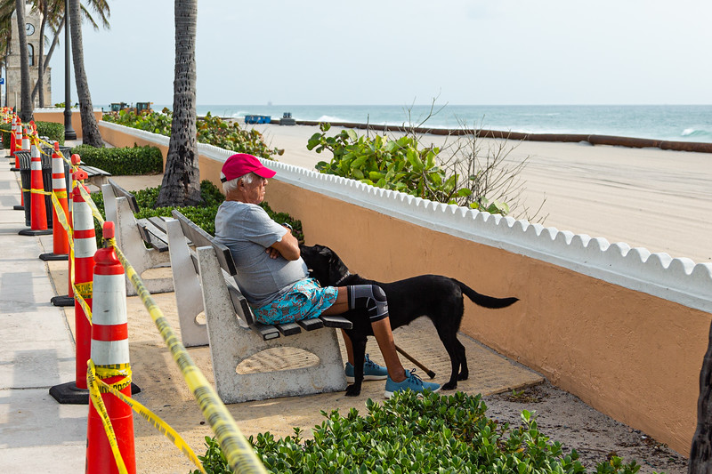 A man sits with his dog behind the barricade at Midtown Beach in Palm Beach, Friday, April 24, 2020. [JOSEPH FORZANO/palmbeachdailynews.com]
