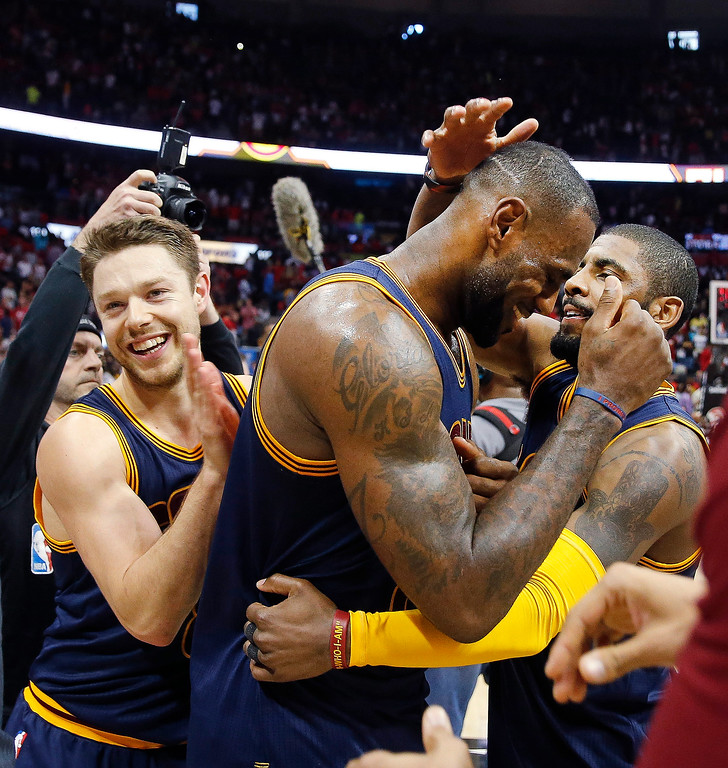 . Cleveland Cavaliers\' LeBron James (23) celebrates with Kyrie Irving, right, and Matthew Dellavedova (8) after  Game 4 of the second-round NBA basketball playoff series against the Atlanta Hawks, Sunday, May 8, 2016, in Atlanta. Cleveland won 100-99 and won the best-of-seven series 4-0. (AP Photo/John Bazemore)