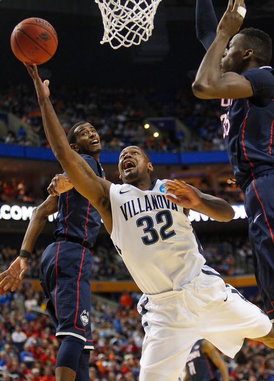 . Villanova\'s James Bell (32) drives past Connecticut\'s Amida Brimah (35) during the first half of a third-round game in the NCAA men\'s college basketball tournament in Buffalo, N.Y., Saturday, March 22, 2014. (AP Photo/Bill Wippert)