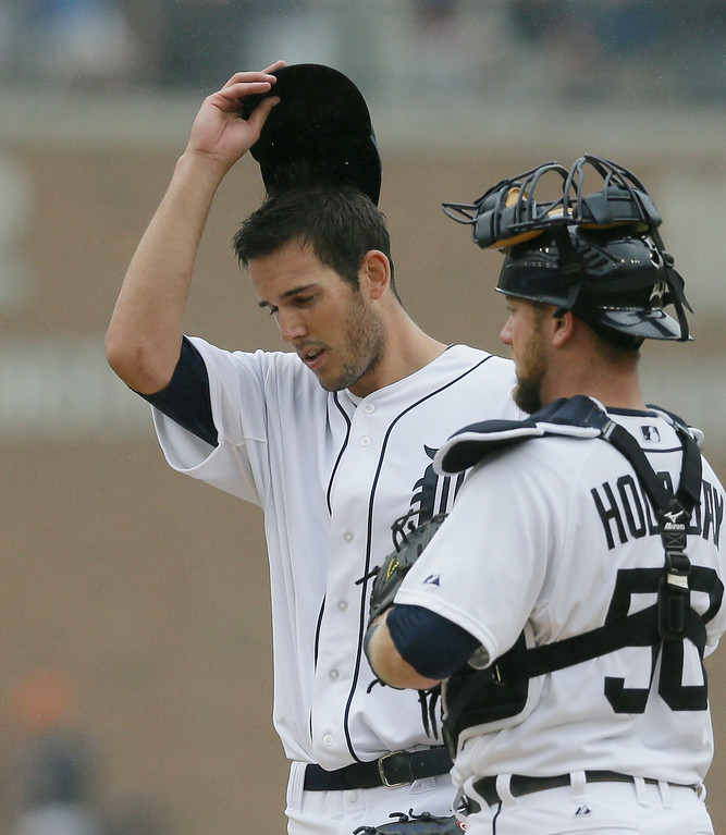 . Detroit Tigers starting pitcher Drew VerHagen wipes his face after giving up three runs during the fifth inning in the first baseball game of a doubleheader against the Cleveland Indians, Saturday, July 19, 2014, in Detroit. Standing with VerHagen is catcher Bryan Holaday. (AP Photo/Carlos Osorio)