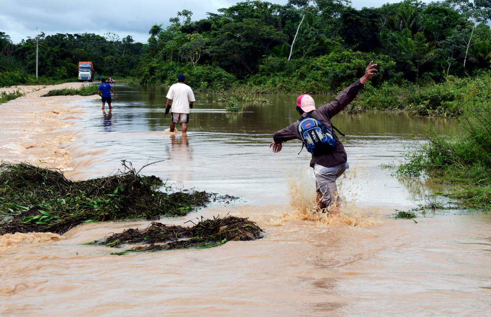. Locals wade through a highway flooded by the overflowing of the Beni river and heavy rains hitting the country, in Reyes, department of Beni, northeast Bolivia, on February 2, 2014. (AIZAR RALDES/AFP/Getty Images)