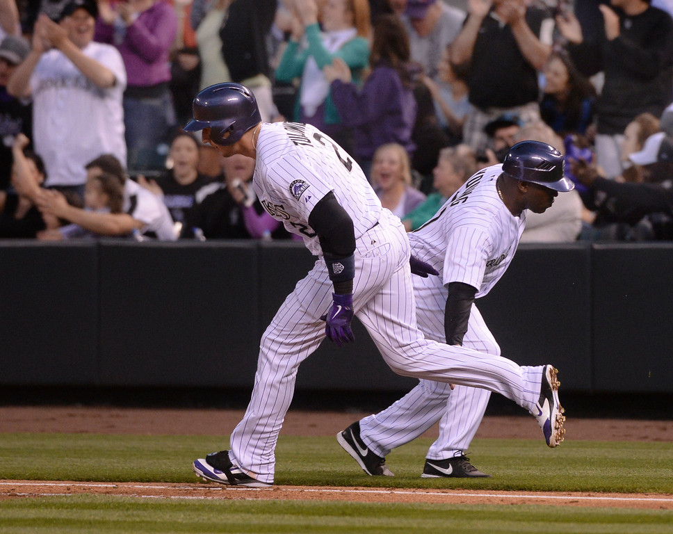 . DENVER, CO - APRIL 18: Troy Tulowitzki slapped hands with Colorado base coach Eric Young after his home run in the second inning. The Colorado Rockies hosted the Philadelphia Phillies Friday night, April 18, 2014 at Coors Field.  (Photo by Karl Gehring/The Denver Post)