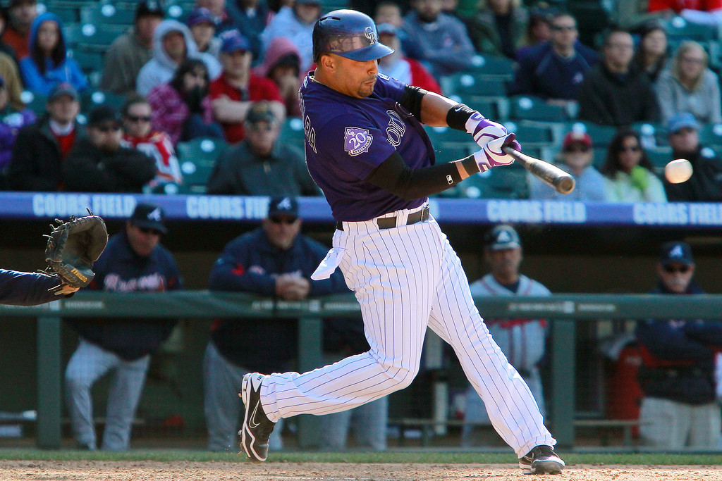 . Colorado Rockies\' Yorvit Torrealba hits an RBI single to score Wilin Rosario to win a baseball game against the Atlanta Braves in the 12th inning, Wednesday, April 24, 2013 in Denver. The Rockies won 6-5. (AP Photo/Barry Gutierrez)
