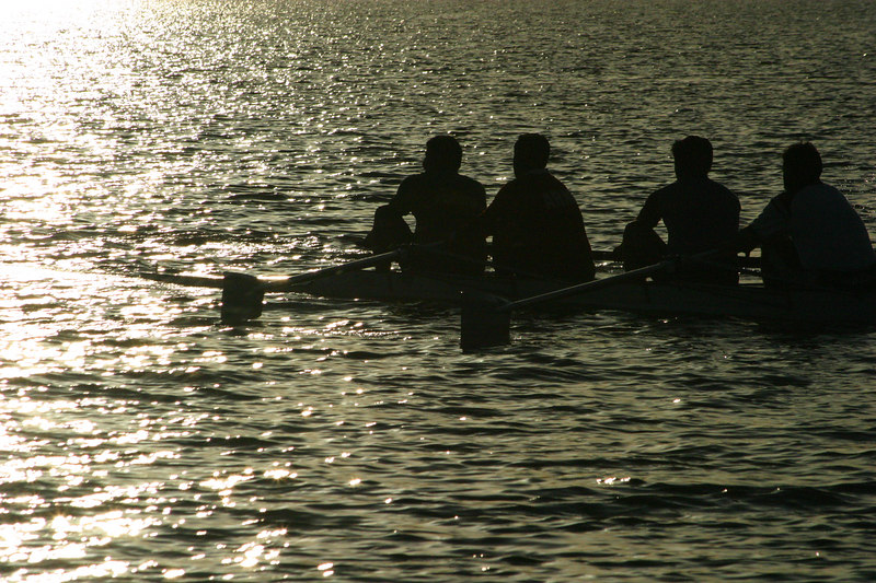 A four rowing at sunset.