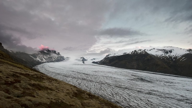 Available in 4k - Summer midnight timelapse over Skaftafellsjökull glacier in Iceland showing clouds and light moving over the landscape