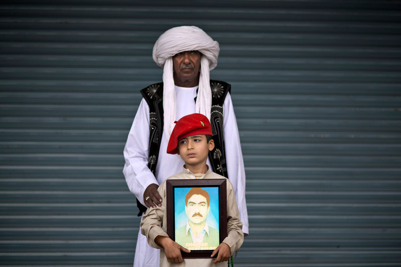 . Mohammed Qadir, 62, and his grandson Meer, 7, pose for a portrait holding a photograph of his dead father Jaleel, who went missing in 2010 and reported dead in 2013, while he and other relatives take a break from a long march protest, in Rawalpindi, Pakistan, Friday, Feb. 28, 2014. They are part of two dozen activists from the impoverished southwestern province of Baluchistan who walked roughly 3,000 kilometers (1,860 miles) to the capital of Islamabad to draw attention to alleged abductions of their loved ones by the Pakistani government. (AP Photo/Muhammed Muheisen)