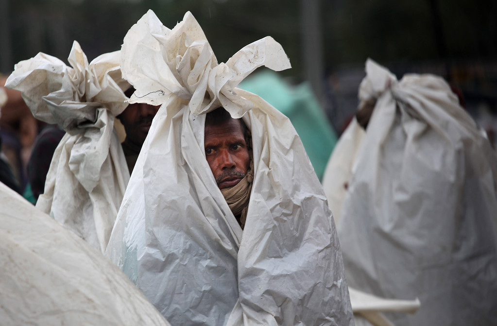 . Migrant workers cover themselves with plastic sheets to shield from the rain, as they camp on a highway after the area they were living in was inundated by floodwaters in Srinagar, India, Saturday, Sept. 6, 2014. Heavy monsoon rains have caused flash floods and landslides.  (AP Photo/Dar Yasin)