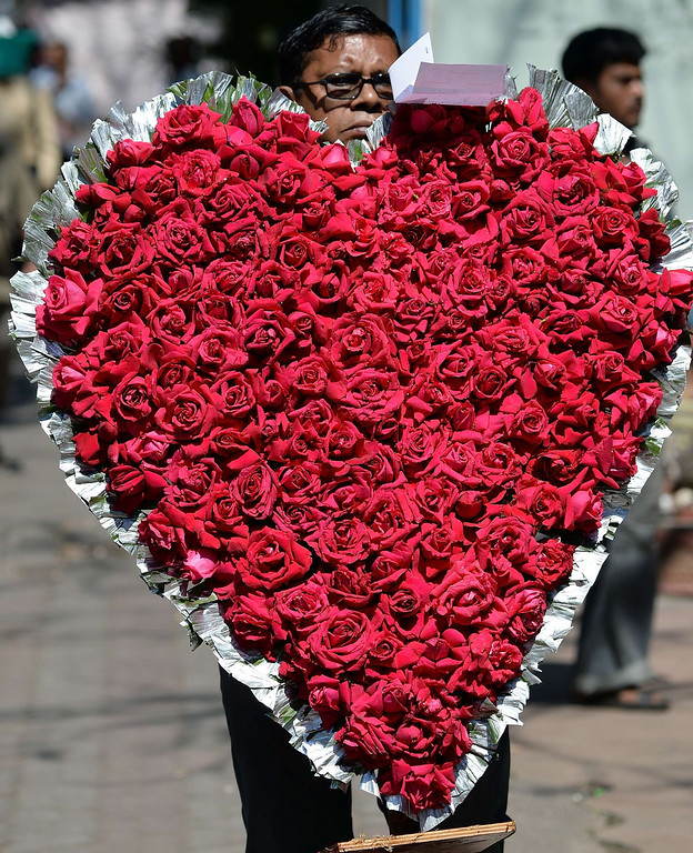 . A florist carries a heart shaped flower arrangement made with roses for delivery on Valentine\'s Day in Mumbai on February 14, 2014. Valentine\'s Day is celebrated with mixed emotions in India as some right-wing Hindu groups view the holiday as a cultural invasion on their way of life. February 14 also falls on the the death anniversary of three of India\'s most revered freedom icons Bhagat Singh, Sukhdev, and Rajguru, who were executed in 1931. AFP PHOTO/INDRANIL MUKHERJEE/AFP/Getty Images