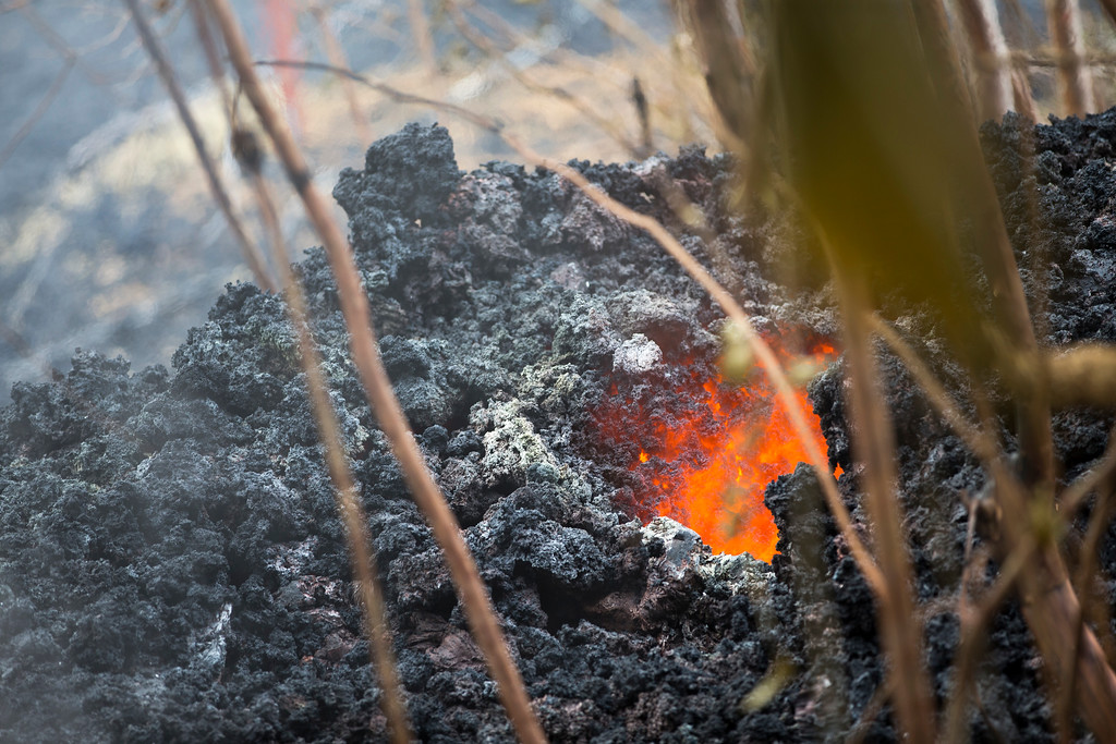 . Lava glows from a vent on a lava bed at the Leilani Estates, Saturday, May 5, 2018, in Pahoa, Hawaii. The Hawaiian Volcanoes Observatory said eight volcanic vents opened in the Big Island residential neighborhood of Leilani Estates since Thursday. (AP Photo/Marco Garcia)