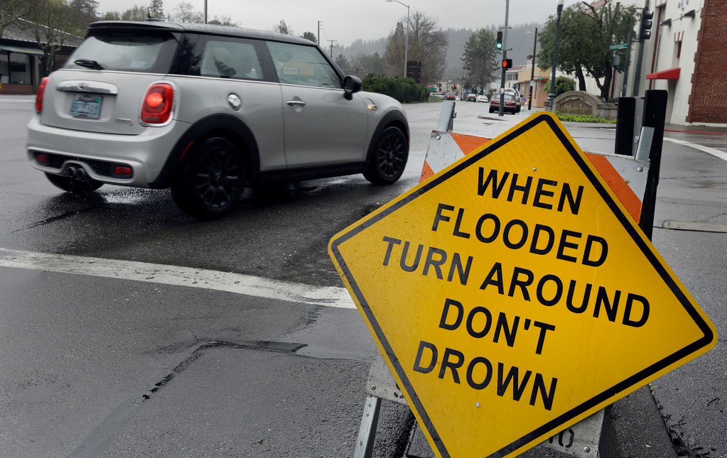 . A sign warning motorists of flooded roads is seen on Tuesday, Feb. 7, 2017, in San Anselmo, Calif. Flash flood watches are in place for parts of Northern California down through the Central Coast as heavy rains swamp roads and threaten to overtop rivers and creeks. The National Weather Service says more than an inch of rain could fall in the San Francisco Bay Area during a series of storms this week. (AP Photo/Ben Margot)
