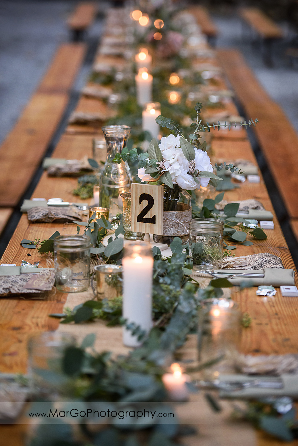 wedding reception tables decorated with green leaves and white flowers at Saratoga Springs Cathedral Grove